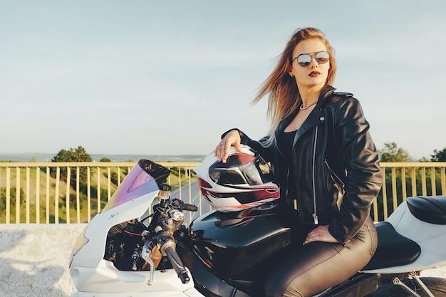 バイクを運転してサングラスを持つ美しい女性 無料写真