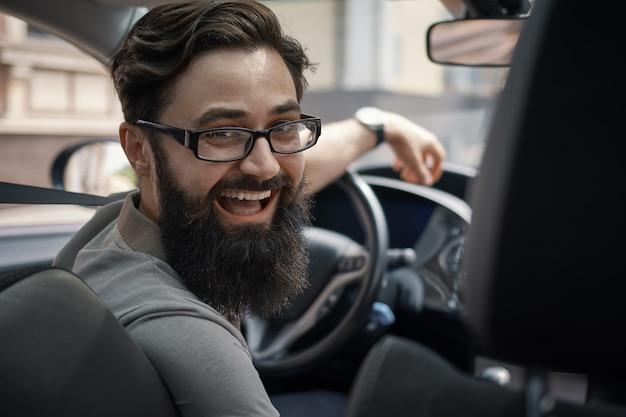 Счастливый харизматичный мужчина за рулем автомобиля Бесплатные Фотографии