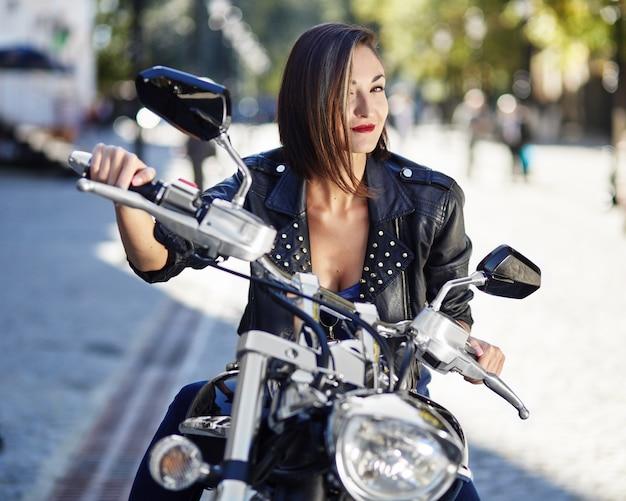 Байкер девушка в кожаной куртке на мотоцикле Бесплатные Фотографии