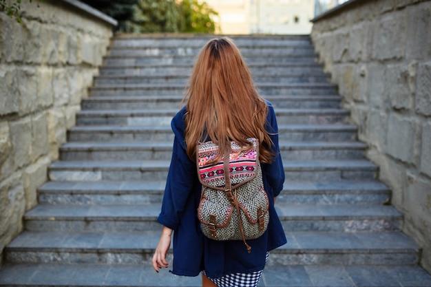 階段を登るバックパックを持つ学生少女 無料写真
