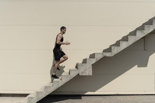 階段に上る健康的な運動男性の完全な長さのショット。 無料写真