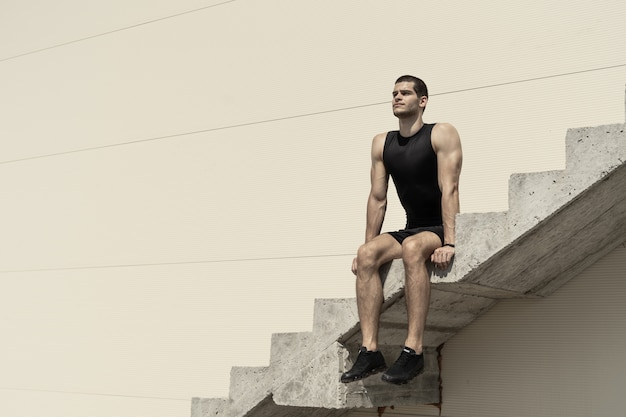 昇順のコンクリート階段の上に座って運動男 無料写真