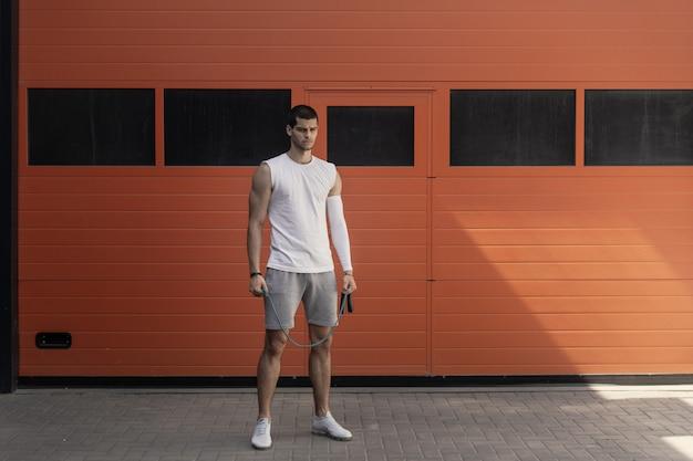 Портрет атлетик, мускулистый мужчина готовится к разминке с прыжки через скакалку Бесплатные Фотографии