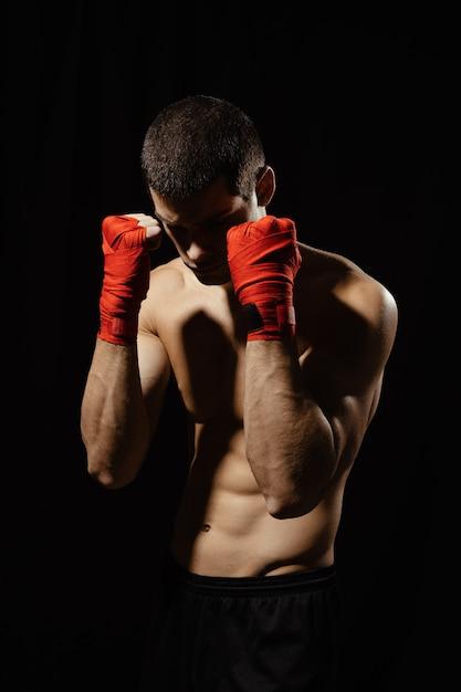 包帯で手で自信を持って防御的な姿勢でポーズをとってボクサー男性戦闘機 無料写真