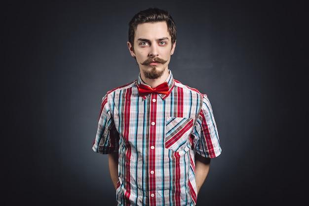 スタジオで格子縞のシャツと蝶ネクタイの男 無料写真