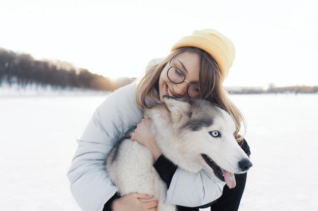 冬の公園でシベリアンハスキー犬と遊んで幸せな若い女の子 無料写真
