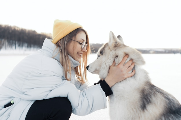 Счастливая маленькая девочка играя с собакой сибирской лайки в парке зимы Бесплатные Фотографии