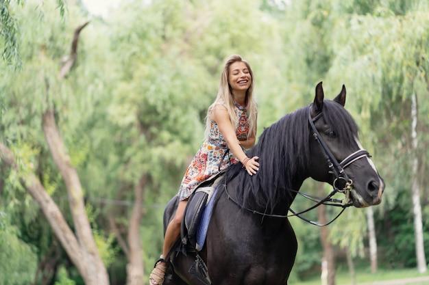 Молодая женщина в ярком красочном платье верхом на черной лошади Бесплатные Фотографии