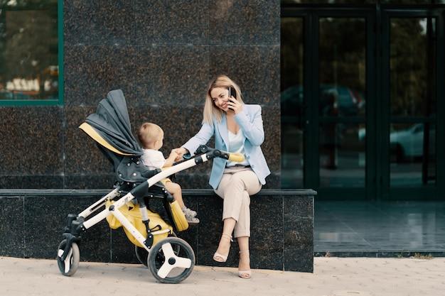 Портрет успешной бизнес-леди в голубом костюме с ребенком Бесплатные Фотографии