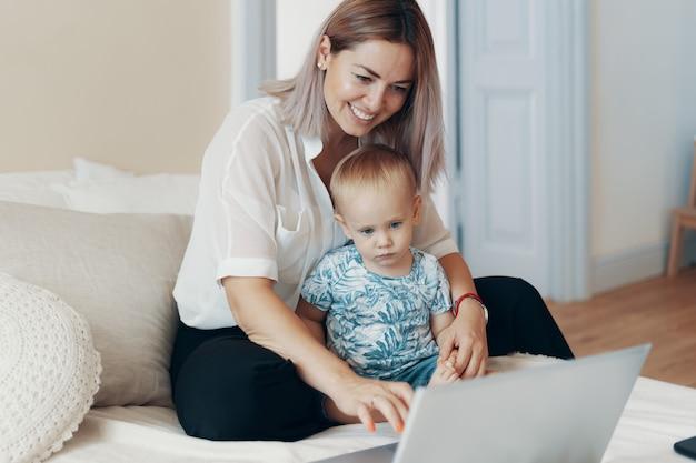 子供と働く現代の女性。マルチタスク、フリーランス、母性のコンセプト 無料写真