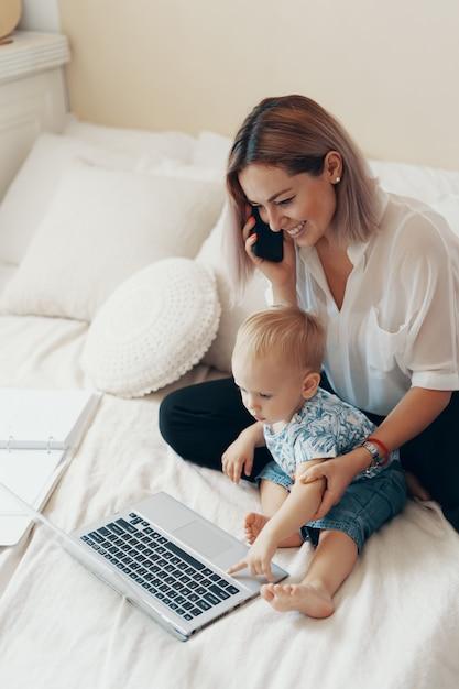 Современная женщина, работающая с ребенком. концепция многозадачности, фриланс и материнства Бесплатные Фотографии