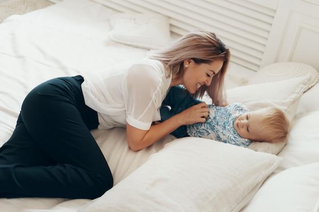 Молодая мать весело смеется, играя в веселые активные игры с милым сыном ребенка в спальне Бесплатные Фотографии