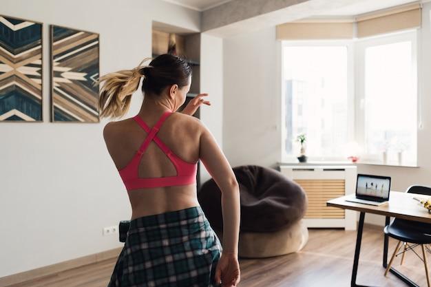ノートパソコンでビデオレッスンに続く家で踊る女性 無料写真