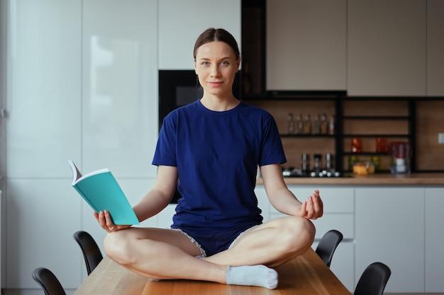 Красивое чтение женщины сидя на таблице в представлениях йоги Бесплатные Фотографии