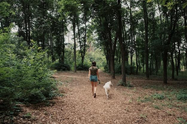 Молодая женщина гуляя с белой лайкой Бесплатные Фотографии