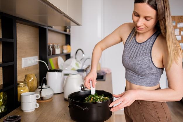 モダンなキッチンで料理をして美しい女性 無料写真