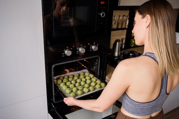 Прекрасно облегающая женщина поставила в духовку поднос с фалафелем Бесплатные Фотографии