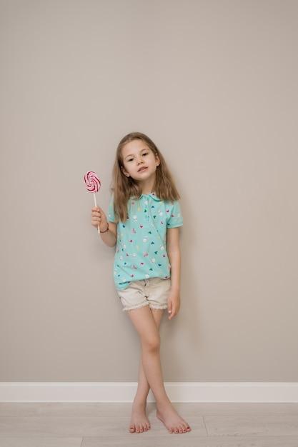 ベージュ色の背景にキャンディーと素敵な女の子 無料写真