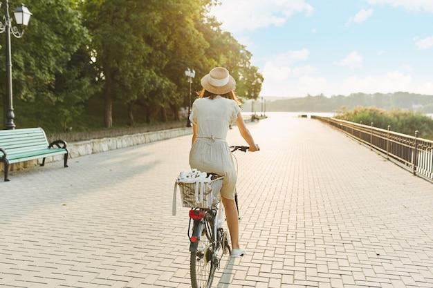 自転車に乗って帽子の魅力的な若いブルネットの屋外のポートレート。 無料写真
