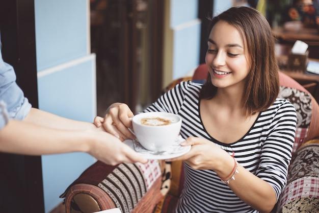 Молодая женщина пьет кофе в городских кафе Бесплатные Фотографии