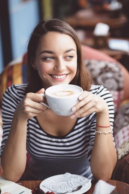 都市のカフェでコーヒーを飲む若い女性 無料写真