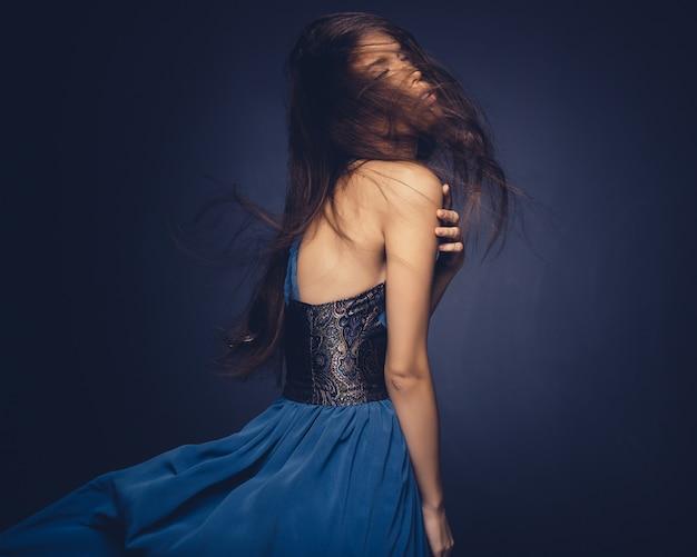 Привлекательная девушка с развевающимися волосами позирует в студии Бесплатные Фотографии