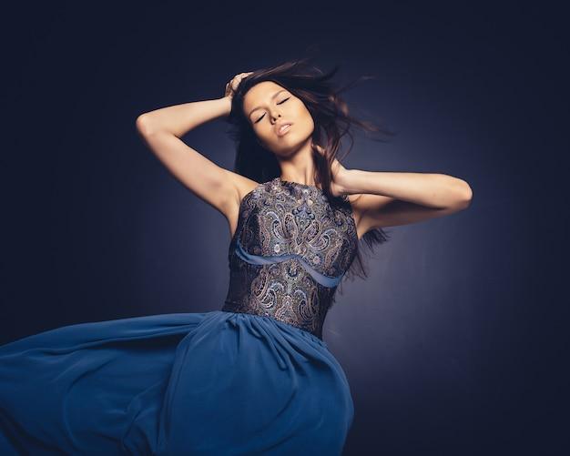 スタジオでポーズをとって髪を飛んで魅力的な女の子 無料写真