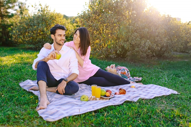 ピクニックを持っている屋外の公園で若いカップル 無料写真