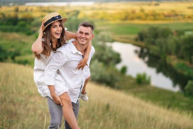 芝生のフィールドで彼女のボーイフレンドによって運ばれている若い女性。夏休みに楽しんでいるカップル。 Premium写真