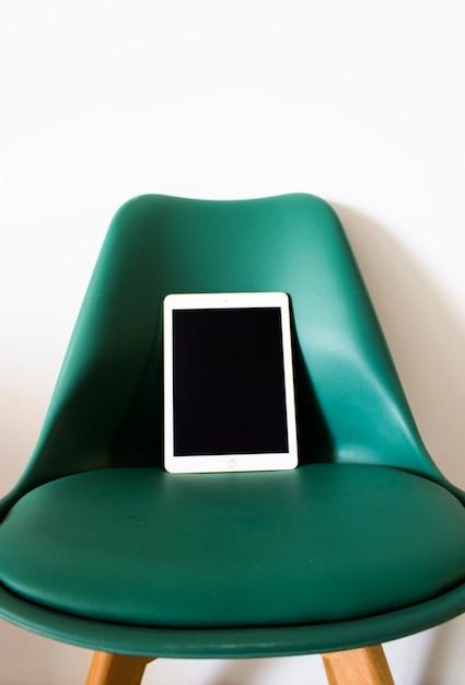 椅子の上にブランクの画面を持つタブレット 無料写真