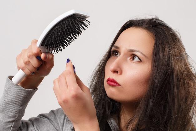 Женщина с растрепанными лохматыми волосами держит в руках расческу Premium Фотографии