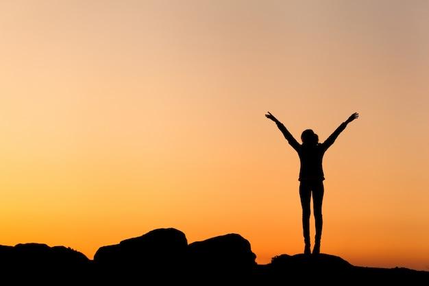 美しいカラフルな空に対して幸せな若い女性のシルエット Premium写真