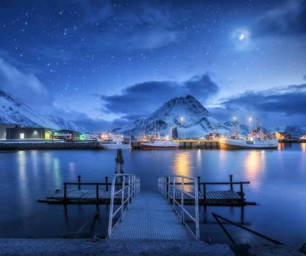 雪山と夜の月と星空に対して海の桟橋の近くの漁船 Premium写真