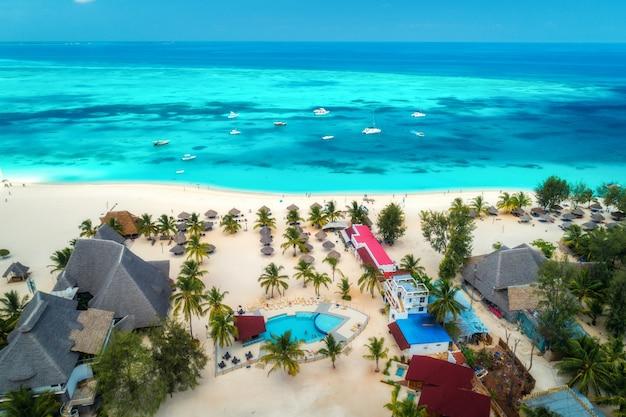 Аэрофотоснимок тропического песчаного пляжа с пальмами и зонтиками в солнечный день Premium Фотографии
