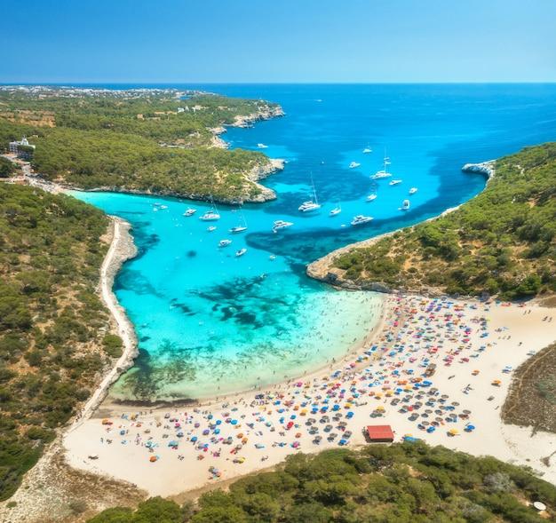 砂浜、青い海、人々、ヨットの空撮 Premium写真