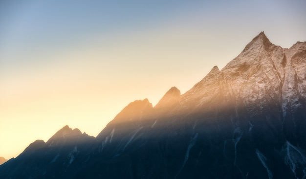 ネパールのカラフルな日の出で山と低い雲 Premium写真