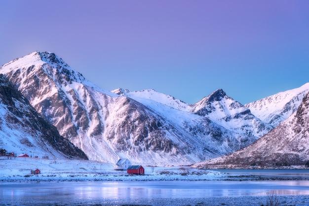 住宅と冬の夕暮れ時に美しい雪に覆われた山々 Premium写真