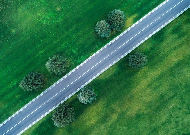Аэрофотоснимок дороги через красивое зеленое поле вечером весной Premium Фотографии