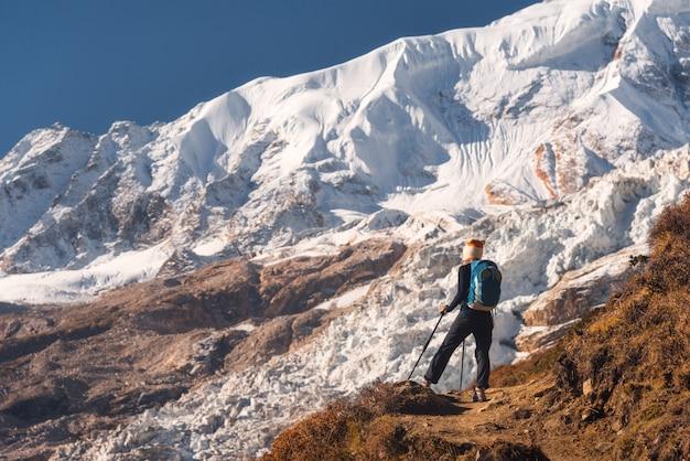 山のピークにバックパックを持つ若い女性に立って、美しい山々と日没の氷河を探して Premium写真