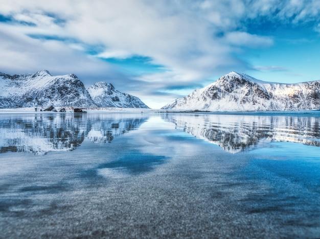 Пейзаж со снежными горами, море, голубое небо с облаками отражается в воде зимой Premium Фотографии