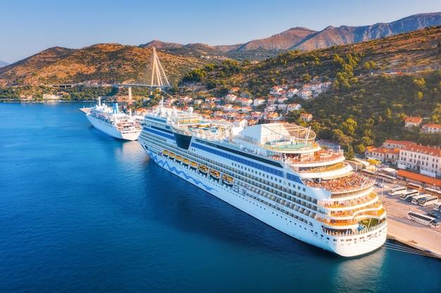港のクルーズ船。日の出の美しい大型船やボートの空撮。港、都市、山、青い海でボートのある風景。 Premium写真