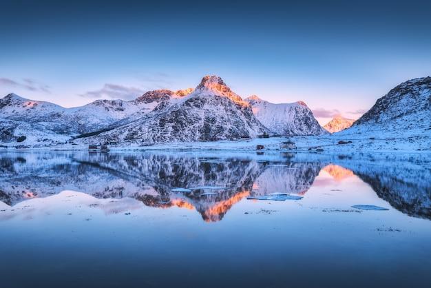 雪に覆われた山々とカラフルな空が夕暮れ時の水に反映 Premium写真