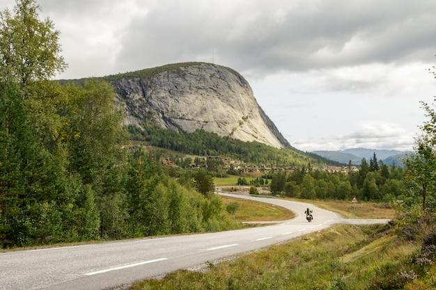 ノルウェー、セデスダールの山に向かって運転する孤独なオートバイの山道 Premium写真