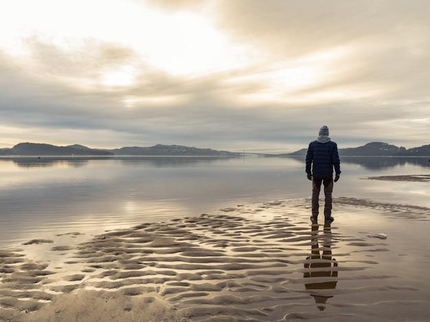 ビーチに立っている男、水の男の反射。穏やかな海、霧、霧。ハムレサンデン、クリスチャンサン、ノルウェー Premium写真