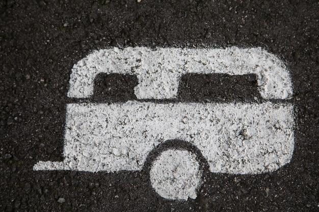 キャラバンの駐車場のアスファルトに描かれた白いキャラバン Premium写真