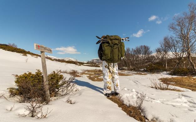 Человек идет к рейнхайм, знак, показывающий путь к рейнхайм в горах довре в норвегии Premium Фотографии