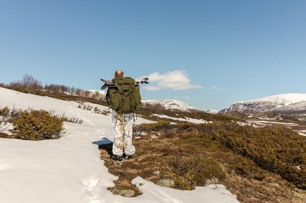 Человек с большими снегоступами в рюкзаке, вид сзади, идет к горам довре в норвегии Premium Фотографии