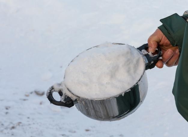 飲料水に溶けるために、雪だらけの鍋を持って男。 Premium写真