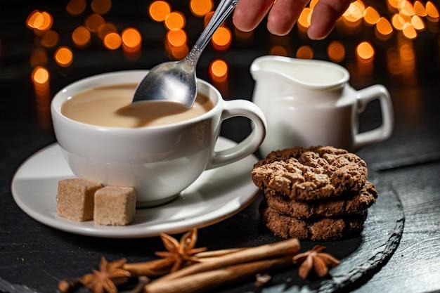 ぼやけたライトにコーヒークッキーとスパイスを保持している手。スタイリッシュな冬のフラットレイアウト。 Premium写真