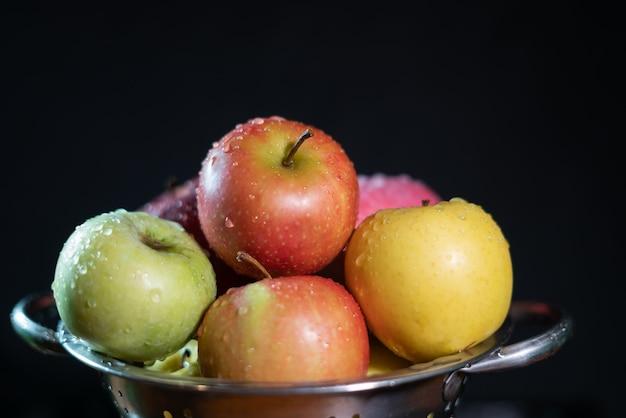 黒の背景に黄色、緑、赤のリンゴ Premium写真